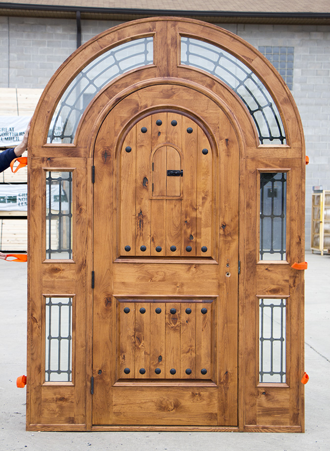Rustic Arched Top Door With Wrought Iron Bars