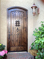 arched exterior door in rustic knotty alder with speakesy door and wrought iron grill