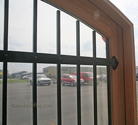 custom arched double doors with iron bars closeup